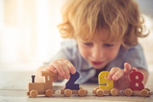 kleiner Junge mit Spielzeug-Lokomotive aus Holz